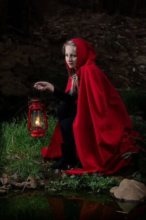 Attractive woman dressed a little red riding-hood cross a stream in a dark forest with a lantern Foto de archivo