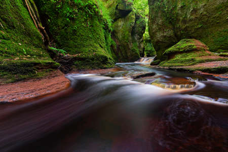 Small river with red water flowing through Finnich Glen landscape photography Reklamní fotografie