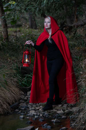 Attractive woman dressed a little red riding-hood cross a stream in a dark forest with a lantern