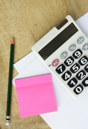 white paper with calculator pencil and memo  on wood table Stock Photo - 9711799