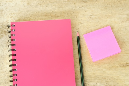 Notebook with a pencil and pink memo on wood table photo