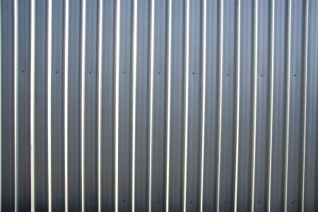 Corrugated metal sheet fence with natural grainy texture photo