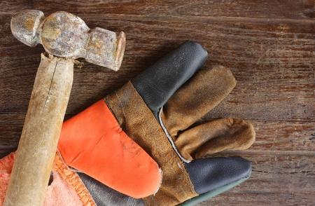 jornada de trabajo: guantes viejos Martillo y cuero en el fondo de madera Foto de archivo
