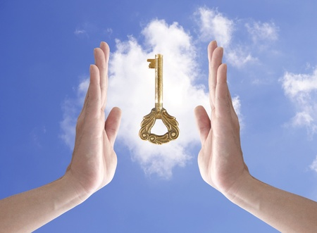 thumb keys: the key to success (hand holding key against blue sky)