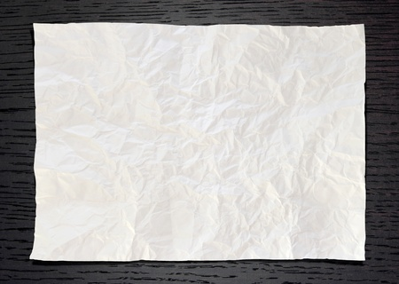 Wrinkled White paper on dark wood background photo