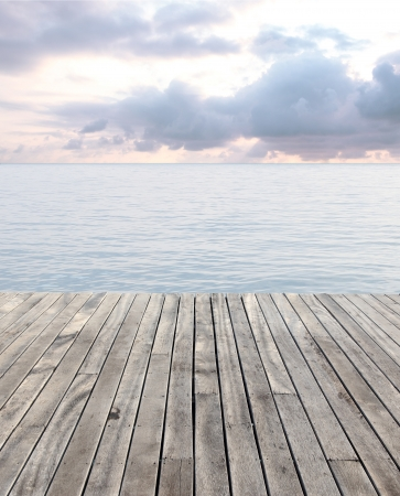 wooden floor and blue sea with waves and cloudy sky Standard-Bild