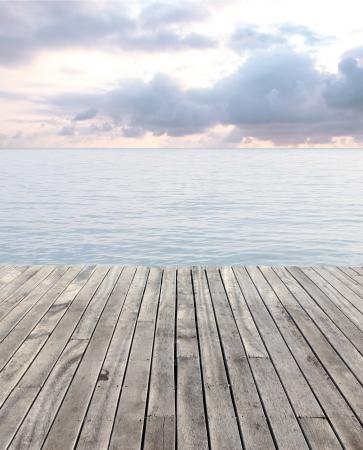 pavimento in legno e mare blu con le onde e il cielo nuvoloso