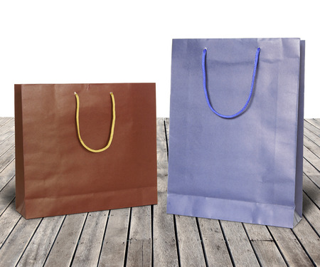 Colorful paper bags on wooden floor against white background photo