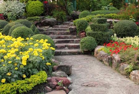 garden marigold: stone walkway in flower garden Stock Photo