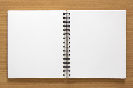 blank spiral notepad on wood background Imagens
