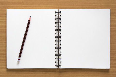 blank spiral notepad and pencil on wood background. Stock Photo