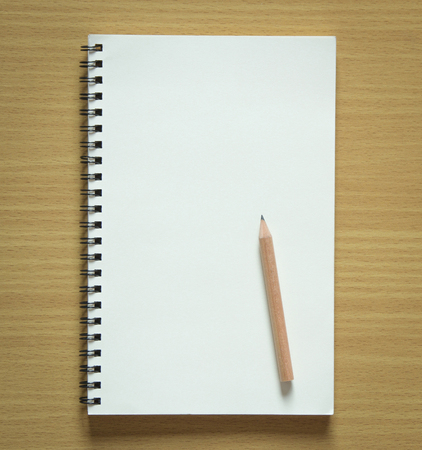 copybook: blank spiral notebook and pencil on wood background