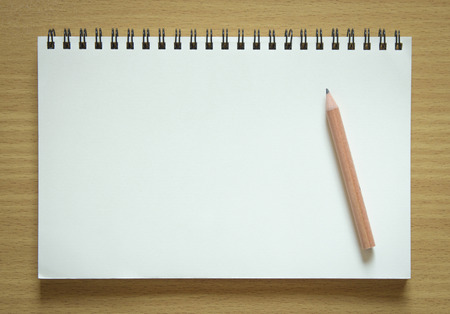 blank spiral notebook and pencil on wood background photo