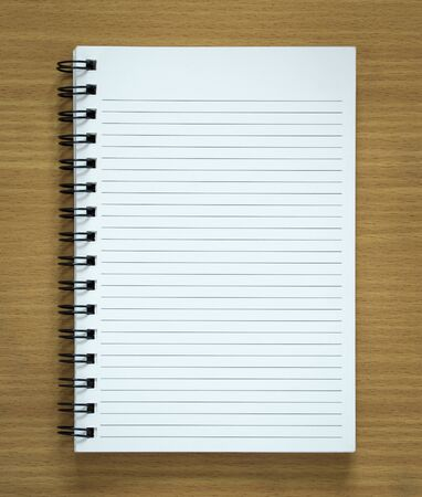 blank spiral notepad on wood background photo