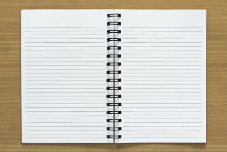 木材の背景にスパイラル ノートを開く