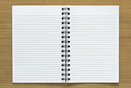 open spiral notebook on wood background