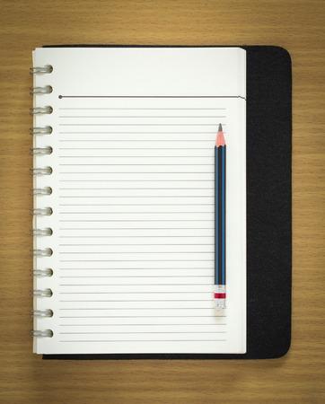 libro abierto: cuaderno de espiral en blanco y un lápiz sobre fondo de madera Foto de archivo