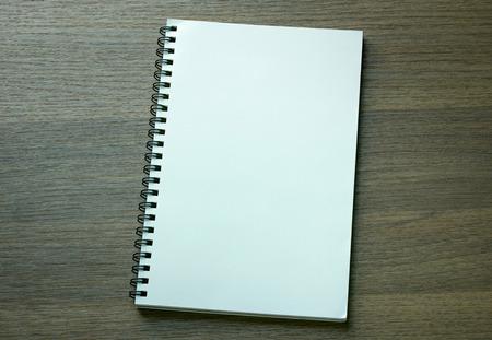 espiral: cuaderno espiral en blanco sobre fondo de madera oscura