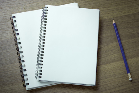 blank book cover: blank spiral notebook and pencil on dark wood background