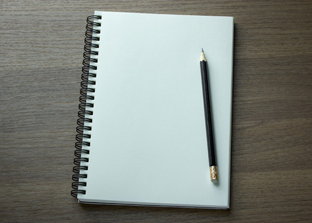 sketch book: blank spiral notebook and pencil on dark wood background
