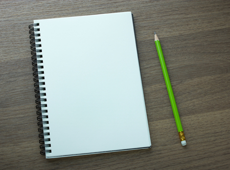 notebooks: blank spiral notebook and pencil on dark wood background