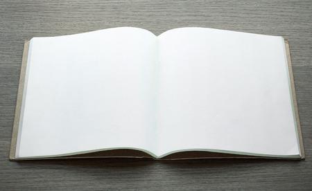 libro abierto: libro abierto en blanco sobre fondo de madera oscura Foto de archivo