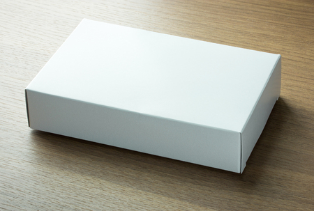 box: blank white paper box on dark wood background