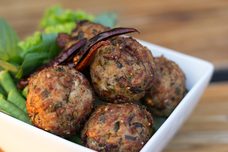 spicy mince pork balls with salad in a white plate on the table. Thai food (Larb Moo Tod) Stockfoto