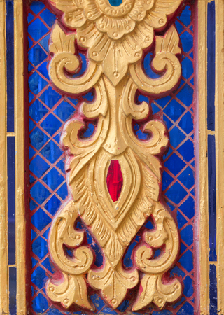 Pattern of gold flower carved on stucco design of native wall, Thai style in temple Stockfoto