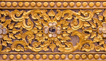 Pattern of gold flower carved on stucco design of native wall, Thai style in temple Redactioneel