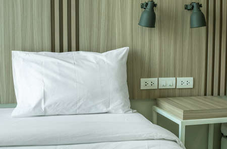 Modern bedroom interior with wall lamp and table