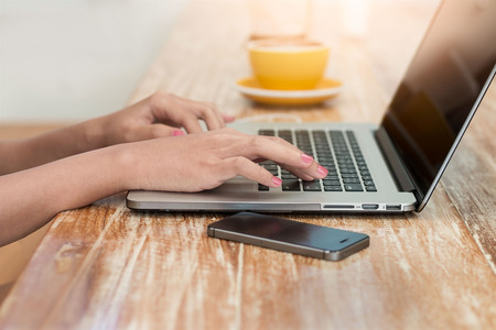 Womans hands using laptop at cafe with smartphone and drinking coffee relaxing on the wooden table