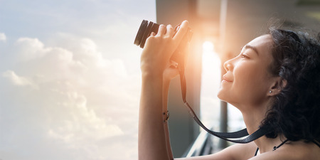 young woman using a camera to take photo outdoors at balcony building Banco de Imagens