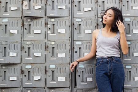 portrait of young woman standing against a old metal lockers background Banco de Imagens