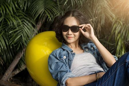 young smiling woman relaxing in sunglasses on park outdoor