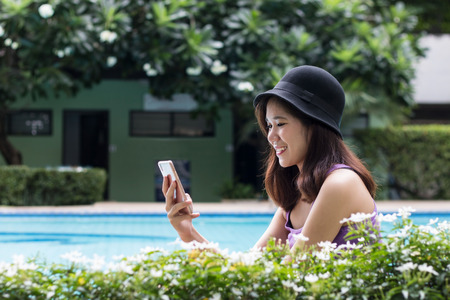 Young pretty woman relaxing with smartphone at poolside garden in resort