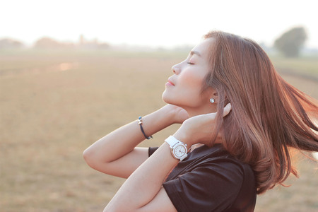 woman relaxing and touch long hair on meadow nature