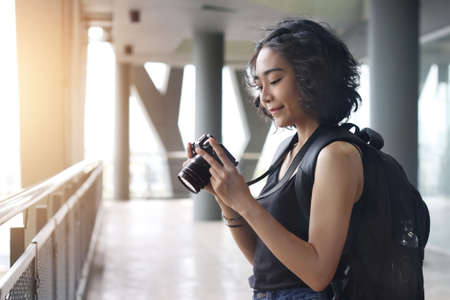 Young woman traveler with back pack taking a photo on building