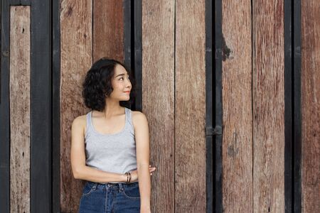 portrait of young woman standing against a wooden wall background