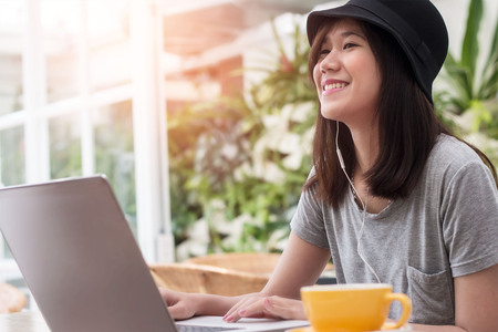 young hipster woman using laptop and listening music with earphone in coffee shop background