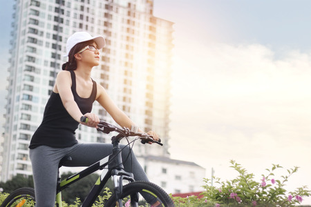 Young woman riding bicycle in city for healthy lifestyle