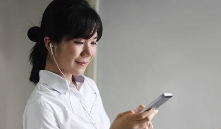 young beautiful asian woman girl in casual wear relaxing and listening music headphones indoor Banco de Imagens