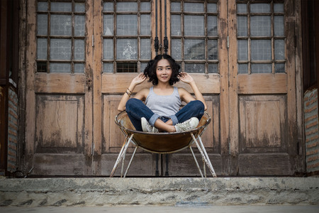 Young woman with smiling in fashion style relax on the chair on old retro door background