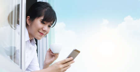 young woman using smartphone and drinking coffee through window at the morning