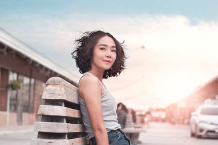 Young woman sitting relaxing in summer sunset street outdoor