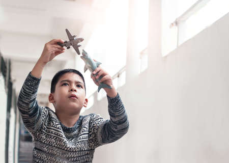 Little boy with imagination playing of shark attacting airplane, copy space Banco de Imagens