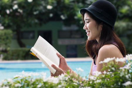 Young asian woman relaxing on poolside reading book Banco de Imagens