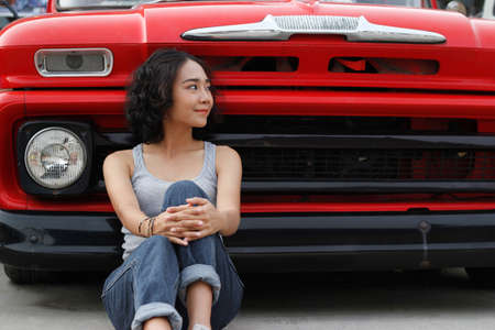 young woman sitting relax on street front car vintage in parking outdoor background Banco de Imagens