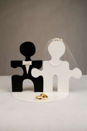 Engaged in hand-shaped puzzle and wedding band. Cake topper photo