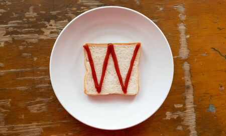 bread of breakfast is written W by ketchup on write plate. A to Z and Number and Special characters set. Stock Photo